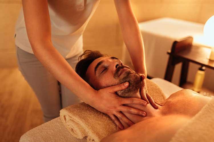 a woman receiving a facial massage in a salon