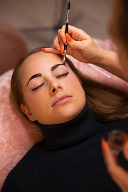 female-specialist-applying-dye-on-client-eyebrow