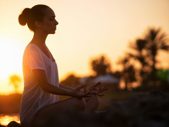 a woman meditating as the sunsets